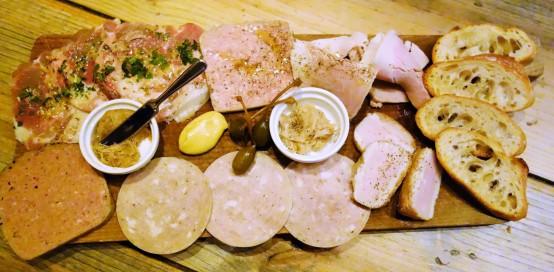 上段左からミュゾー、パテ・ド・カンパーニュ、自家製ハム 中段左の皿が燻製リエット、右の皿が通常のリエット 下段左から鶏レバーのパテ、アライユ、リヨ