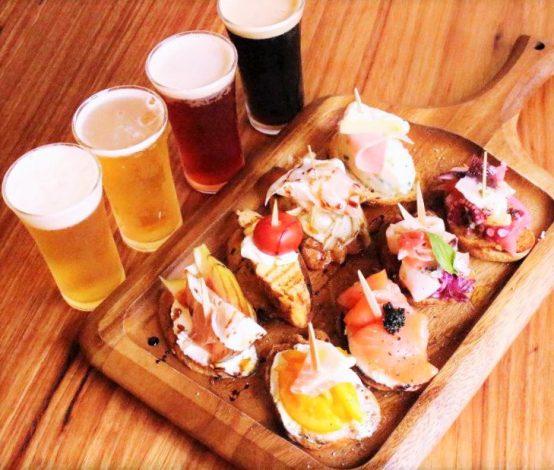 ピンチョス 上段左より生ハムいちじく、トルティーヤ、生ハムときのこのマリネ、ポテハムチーズ 下段左より生ハムマーマレード、スモークサーモン、イカのマリネ、タコレモン ビールは左よりピルスナー、IPA、バーレーワイン、ストロングエール