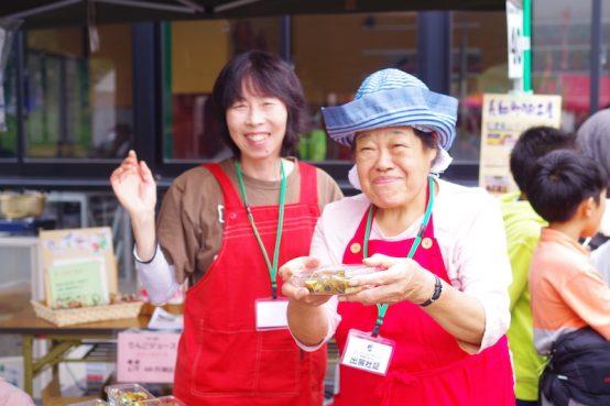 ステキな笑顔で撮影に応じてくれたのは、自慢の自家製漬物など郷土の「食」を提供する地元婦人会の方々。「にぎやかなお祭りが増えて嬉しい」と笑う。