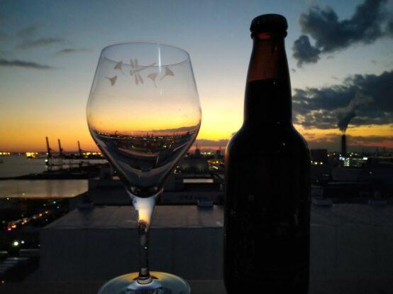 川崎の工業地帯の夕暮れに浮かび始める夜景と東海道BEER川崎宿工場のグラス